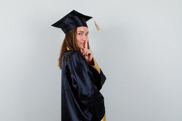 Diplômée en uniforme montrant un geste de silence et à la recherche de sens.