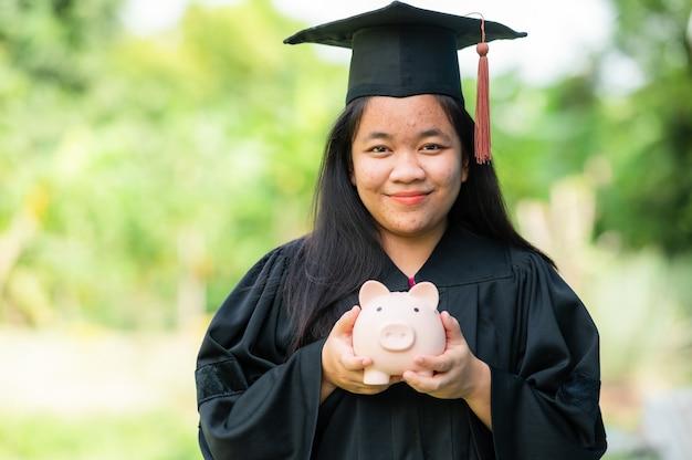 Diplômés détenant le concept d'épargne des tirelires