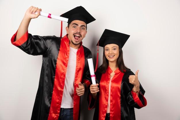 Diplômés frais avec diplôme faisant les pouces vers le haut sur blanc.