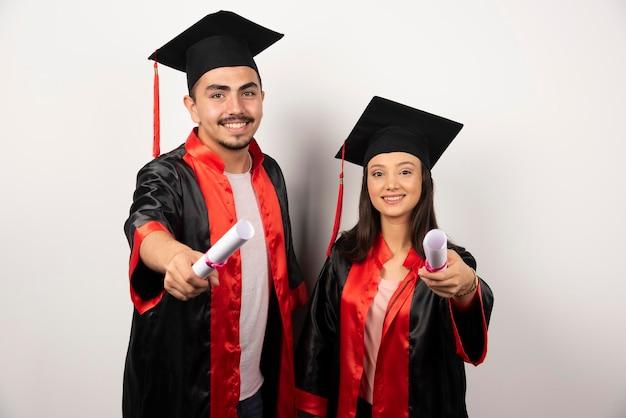 Diplômés frais en robe posant avec diplôme sur blanc.