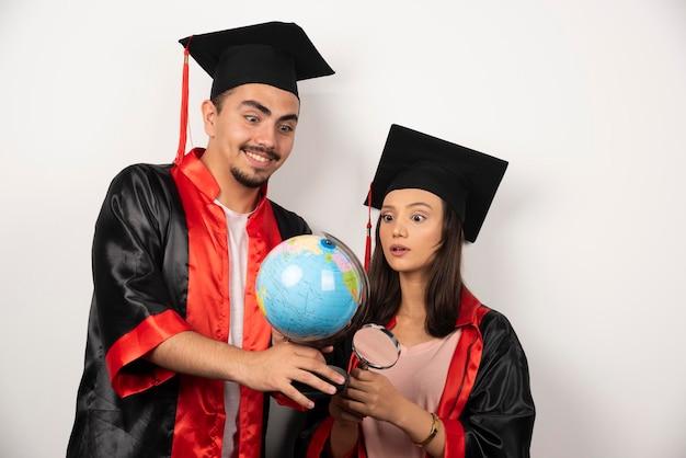 Diplômés frais en robe regardant globe sur blanc.