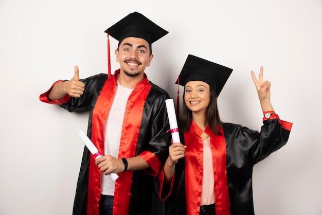 Diplômés frais en robe se sentant heureux avec leur diplôme sur blanc.