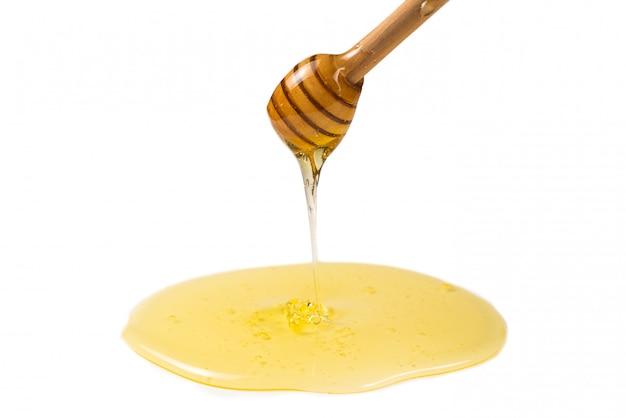 Dipper avec du miel dans la main de la femme.