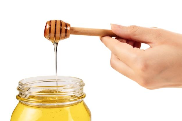 Dipper avec du miel dans la main de la femme