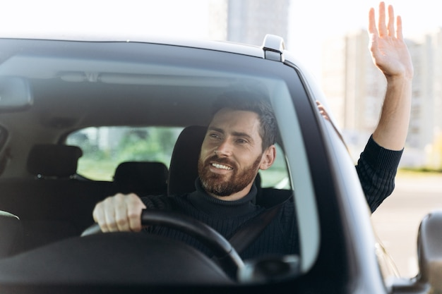 Dire bonjour. beau jeune homme d'affaires souriant assis dans une nouvelle voiture et saluant quelqu'un en conduisant la voiture avec des émotions de plaisir