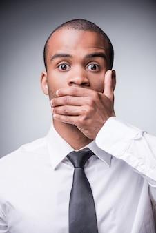 Dire pas de mal. jeune homme africain choqué en chemise et cravate couvrant la bouche avec la main