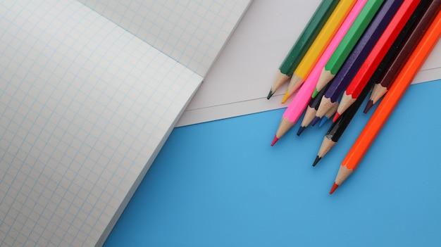 Directement au-dessus de coup de crayons de couleur de livres sur fond bleu