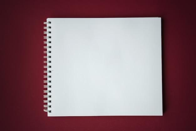 Directement au-dessus de la photo de cahiers à spirale sur fond rouge bureau rouge foncé avec des carnets de croquis.