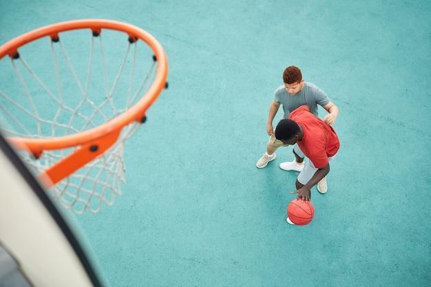 Directement au-dessus de la vue du père noir dribbler le ballon tout en se battant avec son fils pour le faire sous cerceau sur un terrain de sport