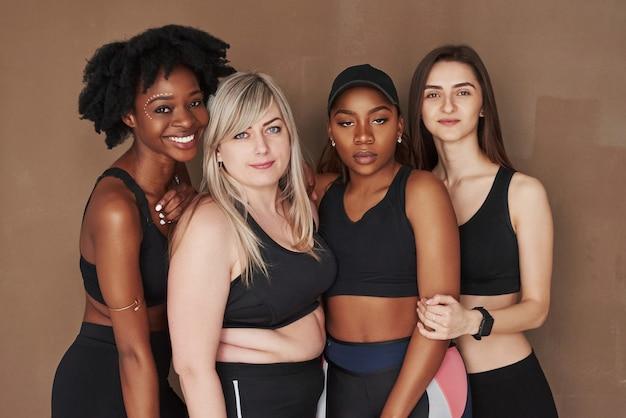 Directement dans la caméra. groupe de femmes multiethniques debout contre l'espace brun