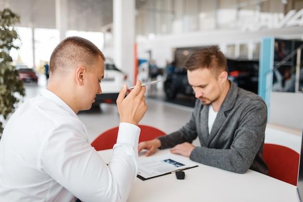 Le directeur et l'acheteur font l'achat d'une nouvelle voiture dans la salle d'exposition.