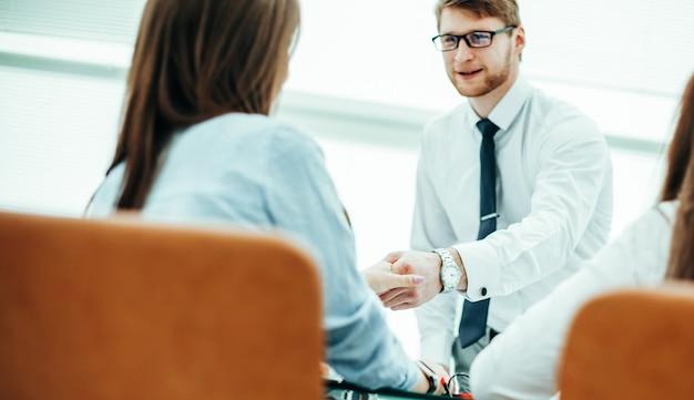 Le directeur de banque et le client se serrent la main après avoir signé un contrat lucratif sur le fond du bureau moderne