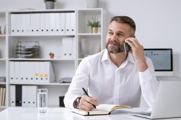Directeur confiant barbu d'une entreprise téléphonant à un client ou à un partenaire tout en résolvant des questions d'organisation au bureau