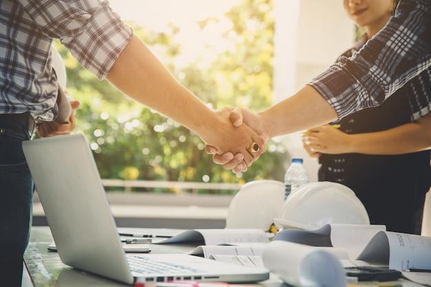 Directeur de la construction et équipe d'ingénieurs serrant la main lors d'une réunion