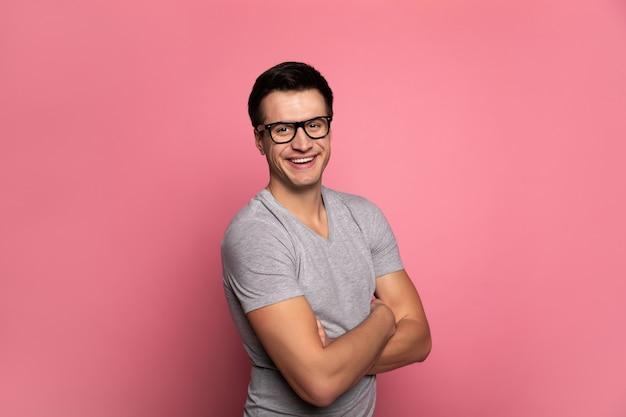 Un directeur créatif.homme gai à lunettes, qui regarde dans la caméra, debout en demi-profil avec les bras croisés.