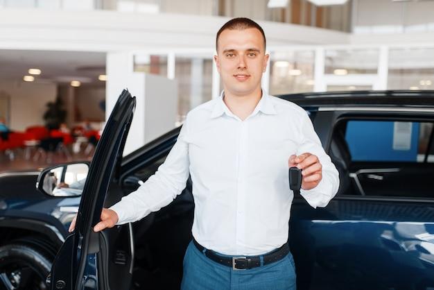 Le directeur donne la clé de la nouvelle voiture dans la salle d'exposition.