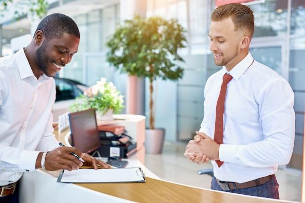 Le directeur donne un contrat de vente de voiture à signer aux clients chez le concessionnaire