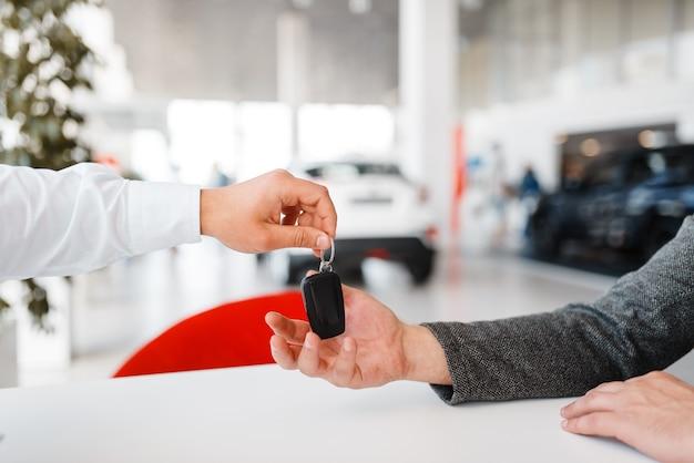 Le directeur donne à la femme la clé de la nouvelle voiture dans la salle d'exposition.