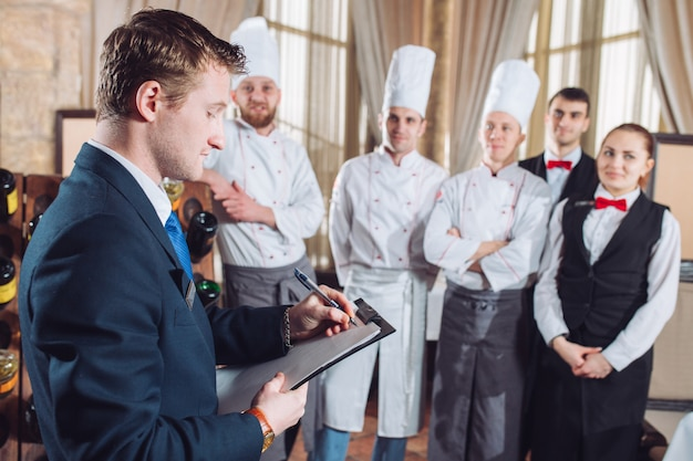 Directeur du restaurant et son personnel en cuisine. interagissant avec le chef cuisinier dans la cuisine commerciale.