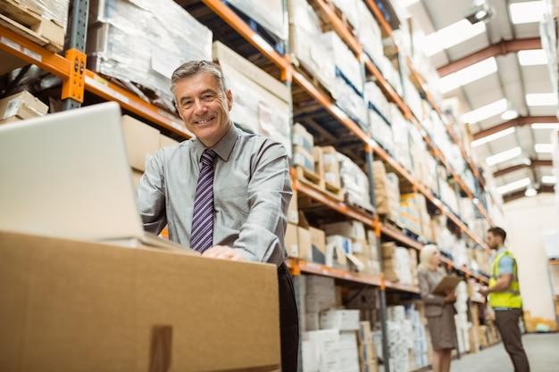 Directeur d'entrepôt souriant travaillant sur un ordinateur portable