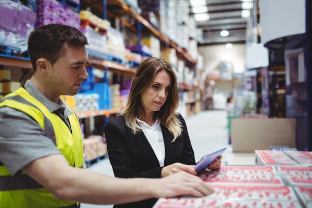 Directeur d'entrepôt et travailleur regardant une tablette dans un entrepôt