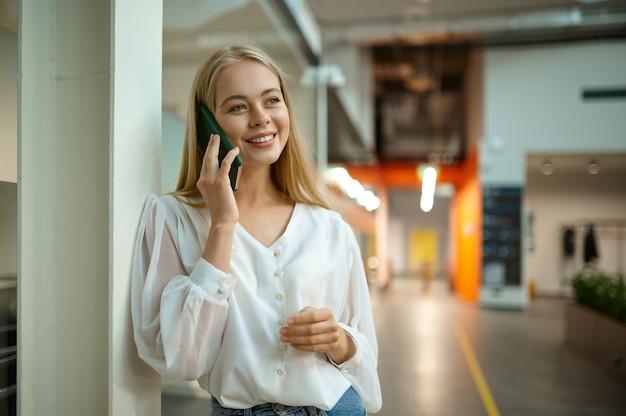 Le directeur féminin souriant parle par téléphone, bureau informatique