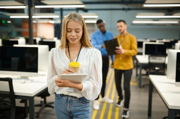 Le directeur féminin tient un ordinateur portable et un café, un bureau informatique