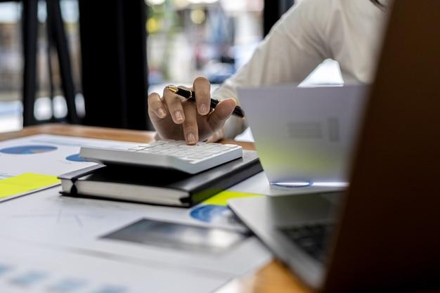 Le directeur financier de l'entreprise utilise une calculatrice, il utilise une calculatrice pour calculer les nombres dans les documents financiers de l'entreprise que les employés du département créent comme documents de réunion.