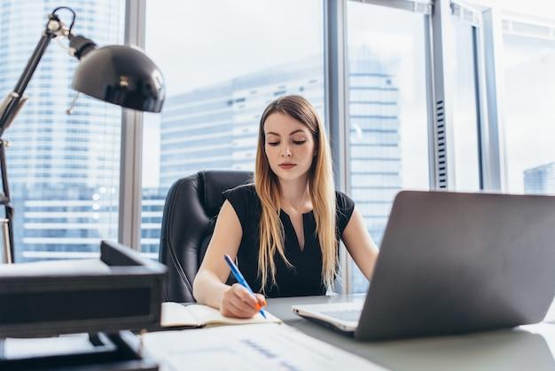 Directeur général féminin assis à son bureau en prenant des notes dans le calendrier écrit avec un stylo et à l'aide de son ordinateur dans un immeuble de bureaux moderne.