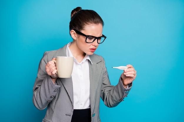 Un directeur indépendant choqué tient une tasse pour vérifier le thermomètre, un symptôme de covid, l'auto-isolement, un fond de couleur bleu isolé