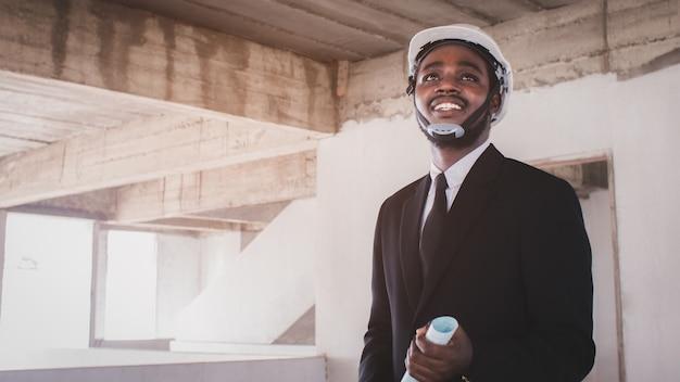 Le directeur d'ingénieur d'architectes africains avec la tablette travaillent ensemble à l'intérieur du chantier de construction