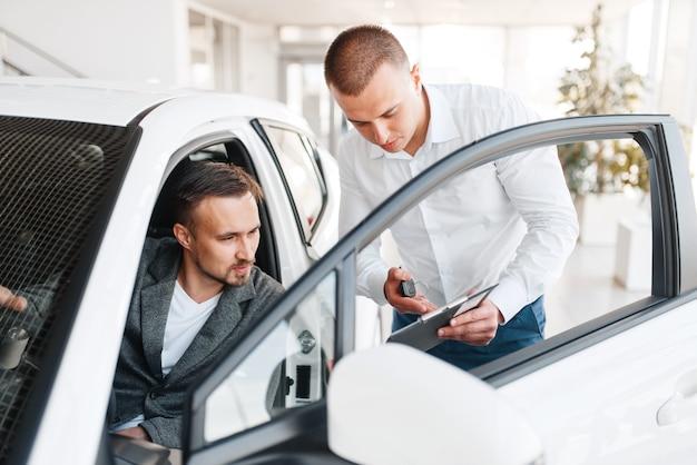 Le directeur montre à l'acheteur le prix de la nouvelle voiture dans la salle d'exposition.