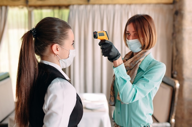 Le directeur d'un restaurant ou d'un hôtel vérifie la température corporelle du personnel avec un appareil d'imagerie thermique.