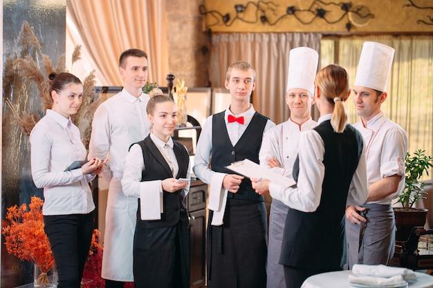 Directeur de restaurant et son personnel dans la cuisine. interagir avec le chef cuisinier dans la cuisine commerciale.