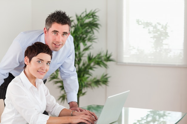 Directeur et sa secrétaire posant avec un ordinateur portable