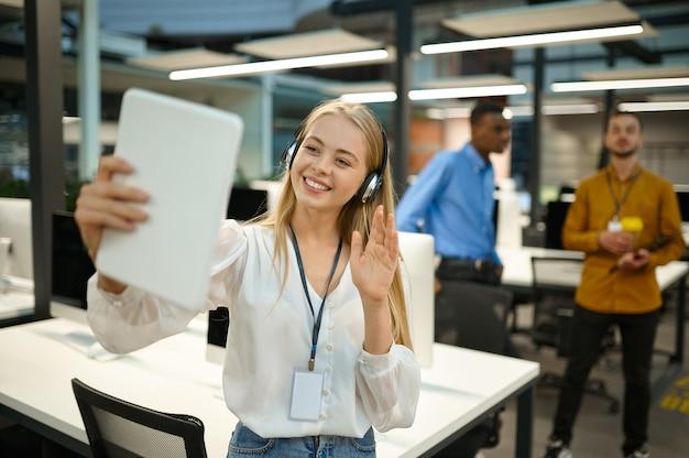 Le directeur tient un ordinateur portable, une vidéoconférence, un bureau informatique