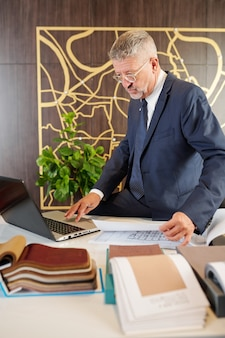 Directeur d'usine de meubles expérimenté vérifiant les plans de meubles et choisissant des échantillons de tissu d'ameublement