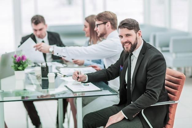 Le directeur des ventes et l'équipe commerciale travaillent avec des rapports financiers sur le lieu de travail au bureau