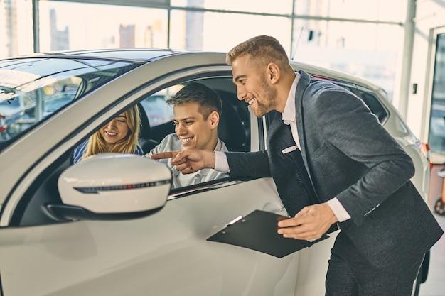 Directeur des ventes souriant décrivant les spécifications d'une nouvelle voiture