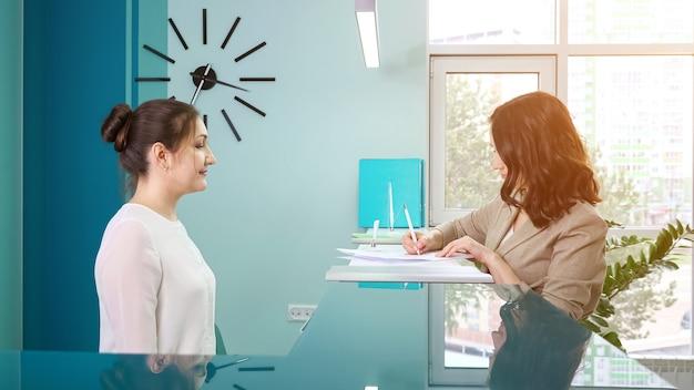 La directrice de bureau de dame en blouse blanche montre le livre d'enregistrement à une cliente debout à la réception dans un hôpital contemporain vue latérale étroite