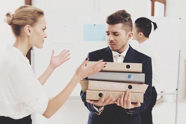 Une directrice des ressources humaines dirige une collègue avec des dossiers et des papiers