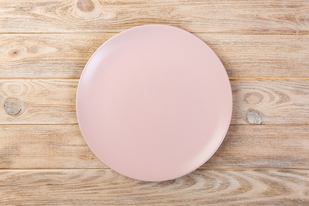 Directy-dessus vide plat rose mat pour le dîner sur fond en bois orange