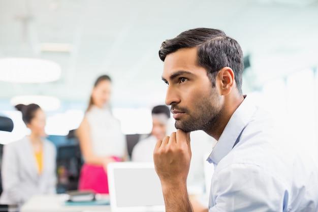 Dirigeant d'affaires réfléchi assis au bureau
