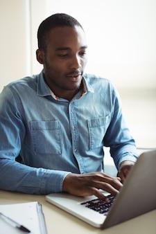 Dirigeant d'entreprise à l'aide d'un ordinateur portable
