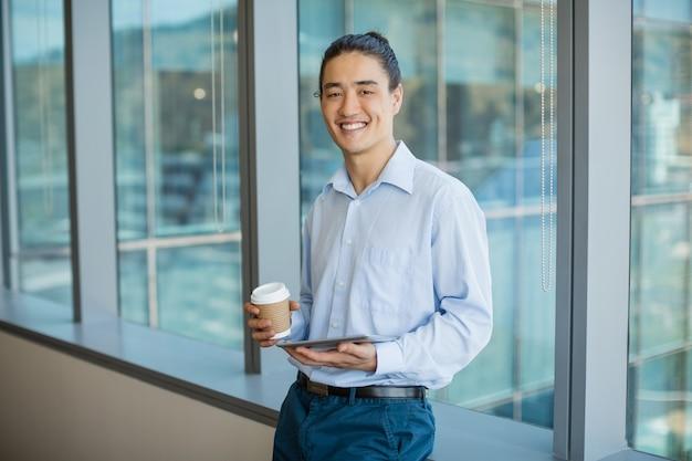 Dirigeant d'entreprise à l'aide de tablette numérique tout en prenant un café dans le couloir du bureau