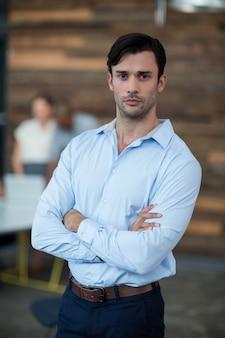 Dirigeant d'entreprise debout avec les bras croisés au bureau