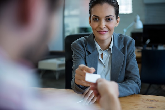 Dirigeant d'entreprise donnant une carte de visite à l'homme pendant l'entrevue