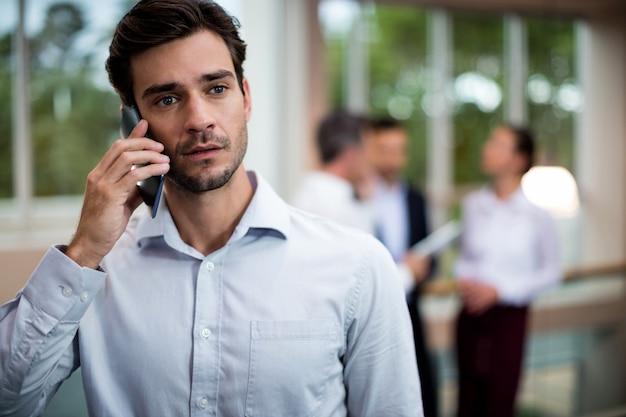 Dirigeant d'entreprise masculin parler sur téléphone mobile