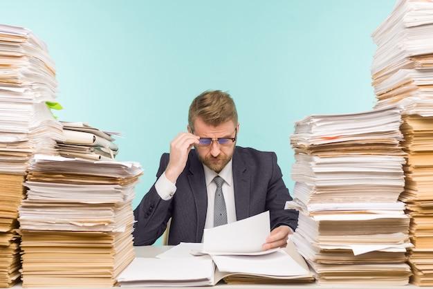 Dirigeant d'entreprise travaillant dans le bureau et des piles de paperasse