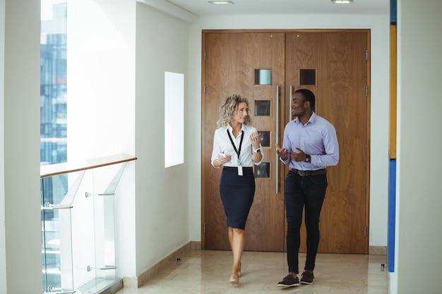 Les dirigeants d'entreprise ayant une discussion en marchant dans le couloir